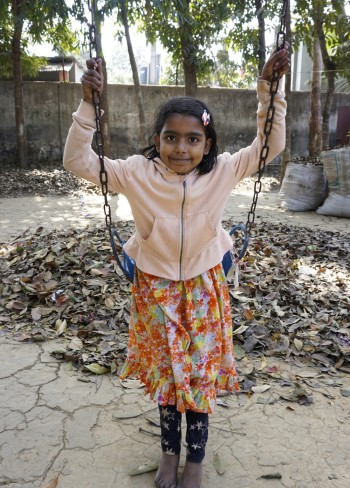 10 year old girl at at Basha smiles into camera while she plays on a swing in an outside courtyard