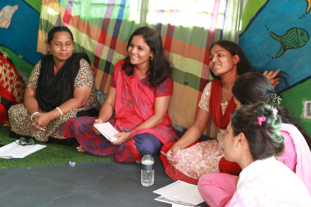 Three day care staff sit on floor listening during child development training session in Dhaka office