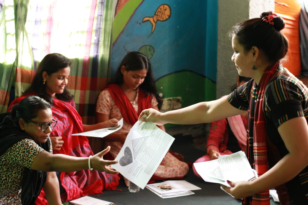 Lipi hands out page with notes on displaying affection to children to a staff member during a staff training session